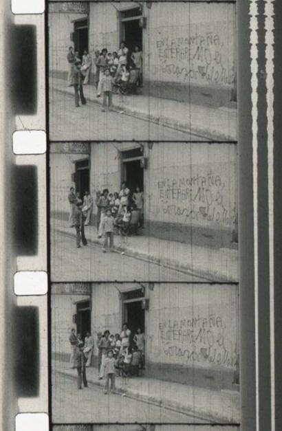 """Figura 2. Nicaragüenses en la calle, en la pared se lee la pinta """"En la montaña enterraremos el corazón del enemigo"""". Carrasco y Gabriel, ¿Cúal es la consigna?, 1978, México. [Fotograma Archivo Escuela Nacional de Artes Cinematográficas de la UNAM (antes CUEC)]"""
