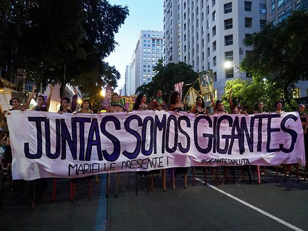 """Fig. 7. Mujeres sostienen un lienzo que dice """"Somos gigantes, Marielle está presente"""" en la marcha del Día Internacional de la Mujer"""